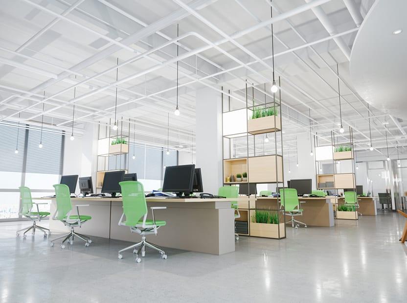 חלל משרדי משותף לבן, עם תקרה גבוהה, שולחנות משותפים, כיסאות ירוקים ומדפים גבוהים מפרידים עם אדניות ירוקות