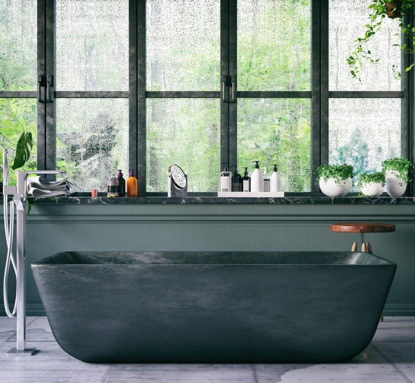 אמבטית מתכת אפורה על רקה חלונות מוארים עם נוף ירוק מבחוץ