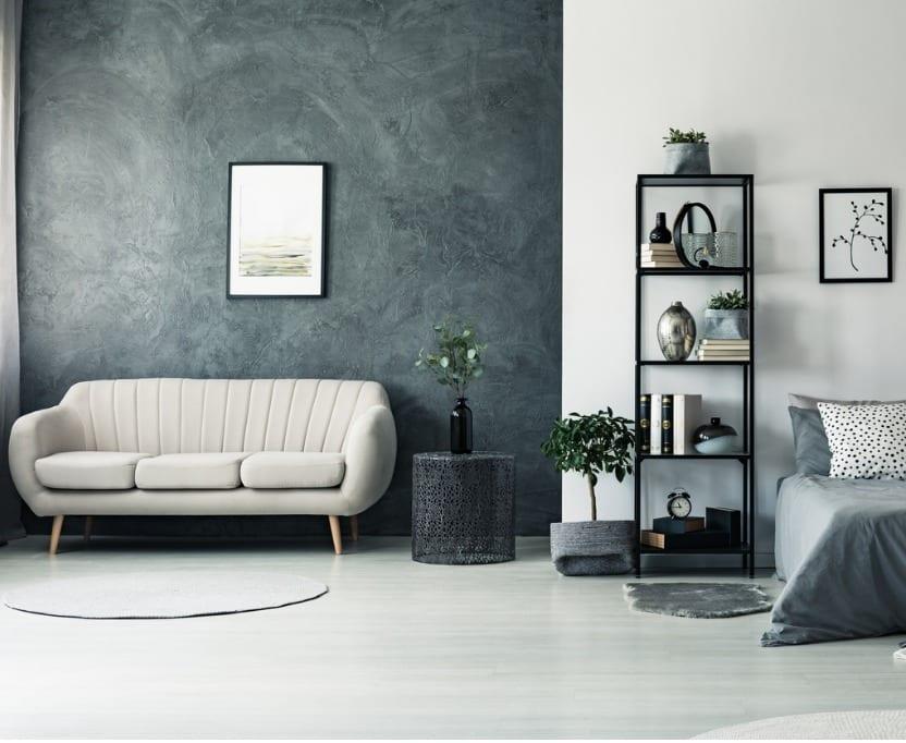 ספה לבנה על רקע קיר אפור-מתכת עם תמונה לבנה מופשטת, ליד הספה סטנד אפור עם עציץ ירוק, ושליש קיר לבן עם כוננית סרים וחצי מיטה ארפורה עם כריות