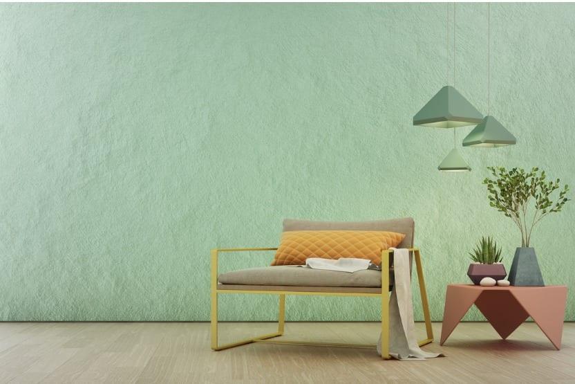 כורסת בז' על רקע קיר ירוק פסטל